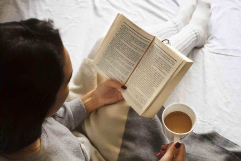 woman reading a book while having coffee, doing a fun activity at home
