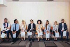group of people who were laid off line up for a new job interview