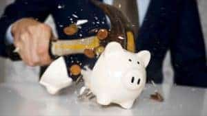 person shattering a piggy bank with a hammer