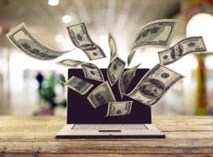 money flying out of a laptop to show how to make money online for beginners