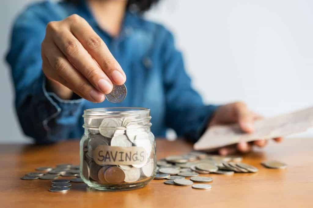 woman placing a quarter into a savings jar to save money every year