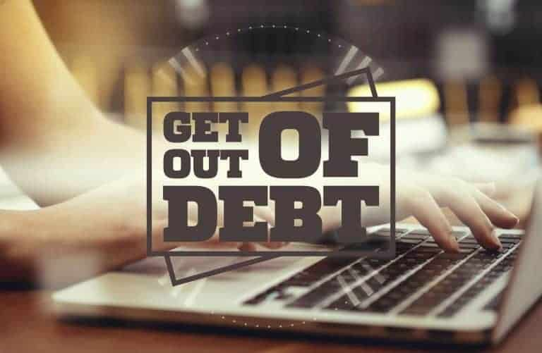 Get out of debt sign in front of someone writing on a laptop