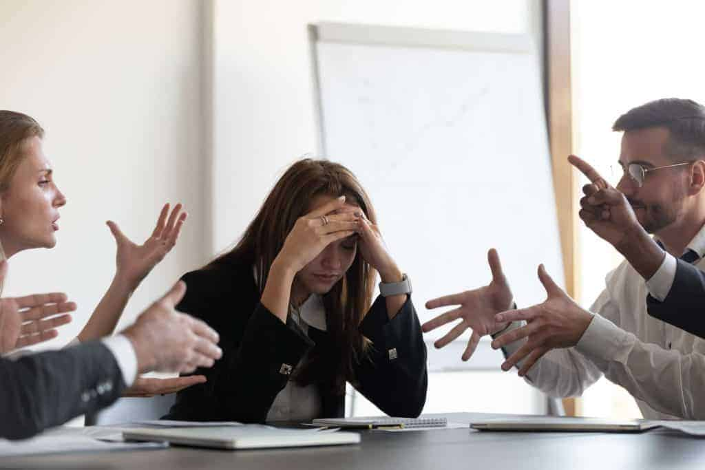 multiple people at a meeting arguing while woman thinks if her job is worth it