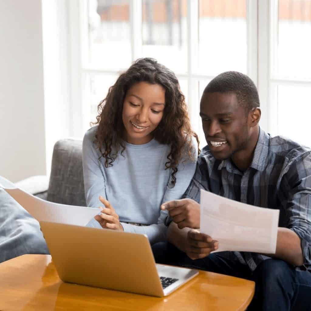 man and woman reviewing budget on a laptop