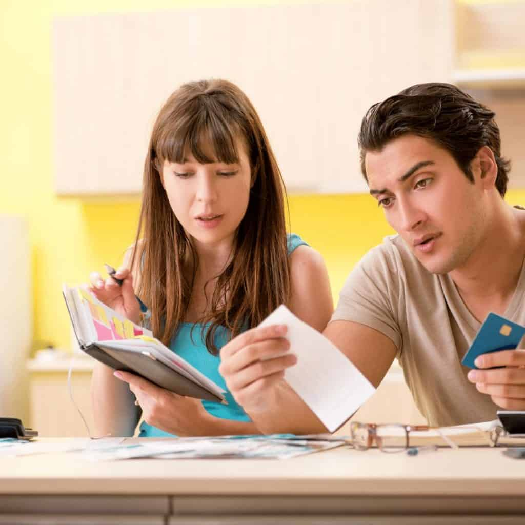 man holding credit card and woman holding bill planner looking at debts