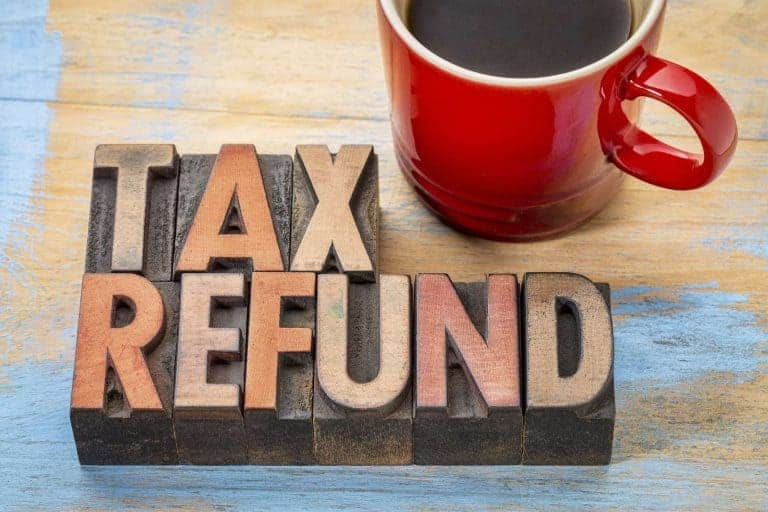 "The words ""Tax Refund"" next to a cup of coffee"