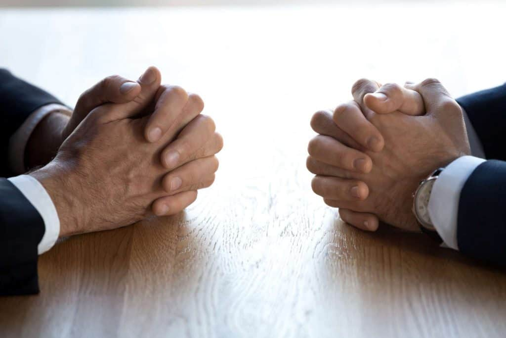 Two sets of interlocked hands on a table of people sitting across from one another