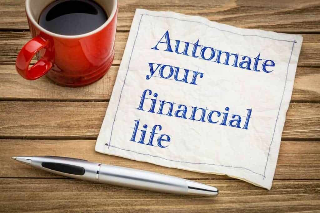 """The words """"automate your financial life"""" written on paper next to a pen and coffee"""
