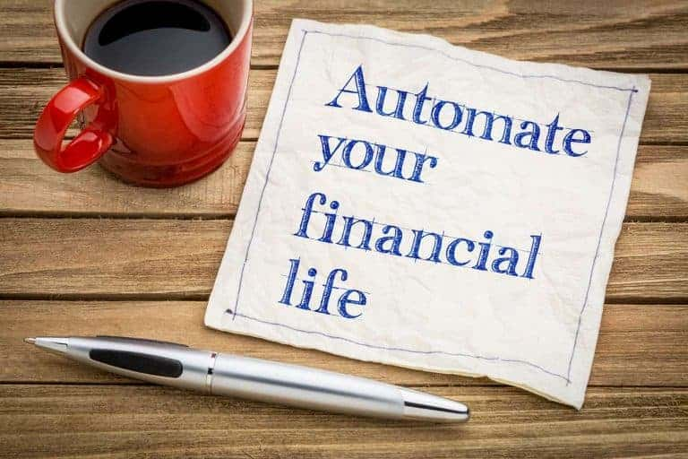"The words ""automate your financial life"" written on paper next to a pen and coffee"