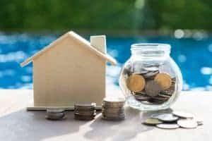 Money in a jar next to a wooden house signifying saving money for a down payment