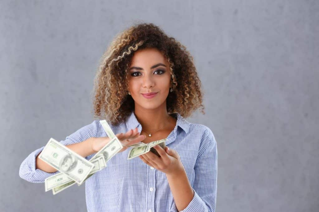 woman with cash after making money from a job where she didn't need a degree
