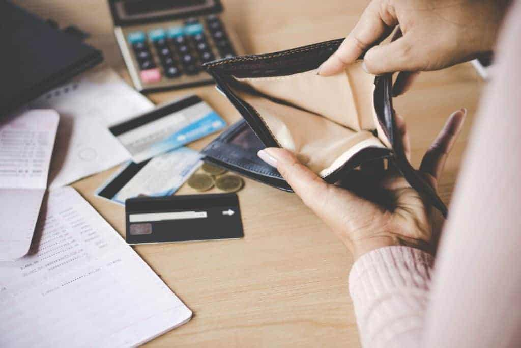 woman holding open an empty wallet with credit cards and papers on desk