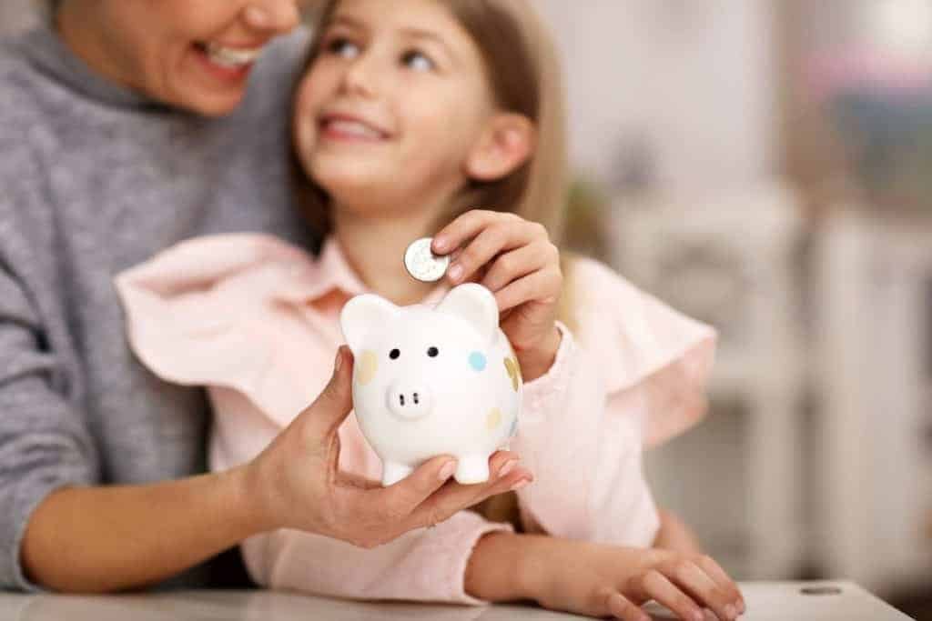 smiling mom and girl with a piggy bank
