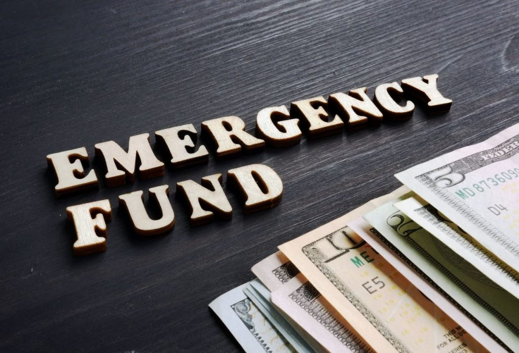 """the words """"emergency fund"""" written near money saved for an emergency"""