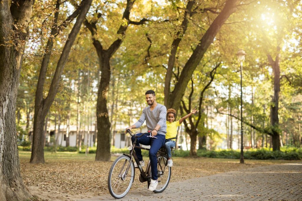 father and child riding a bike as a frugal activity