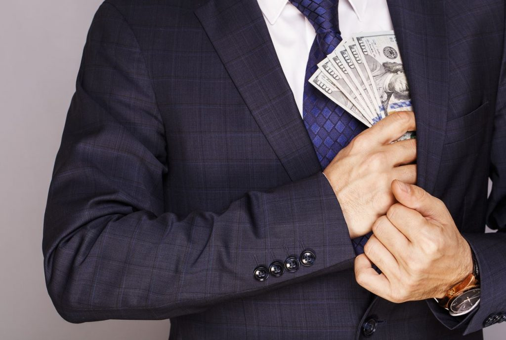 Man holding money he's made with $1,000