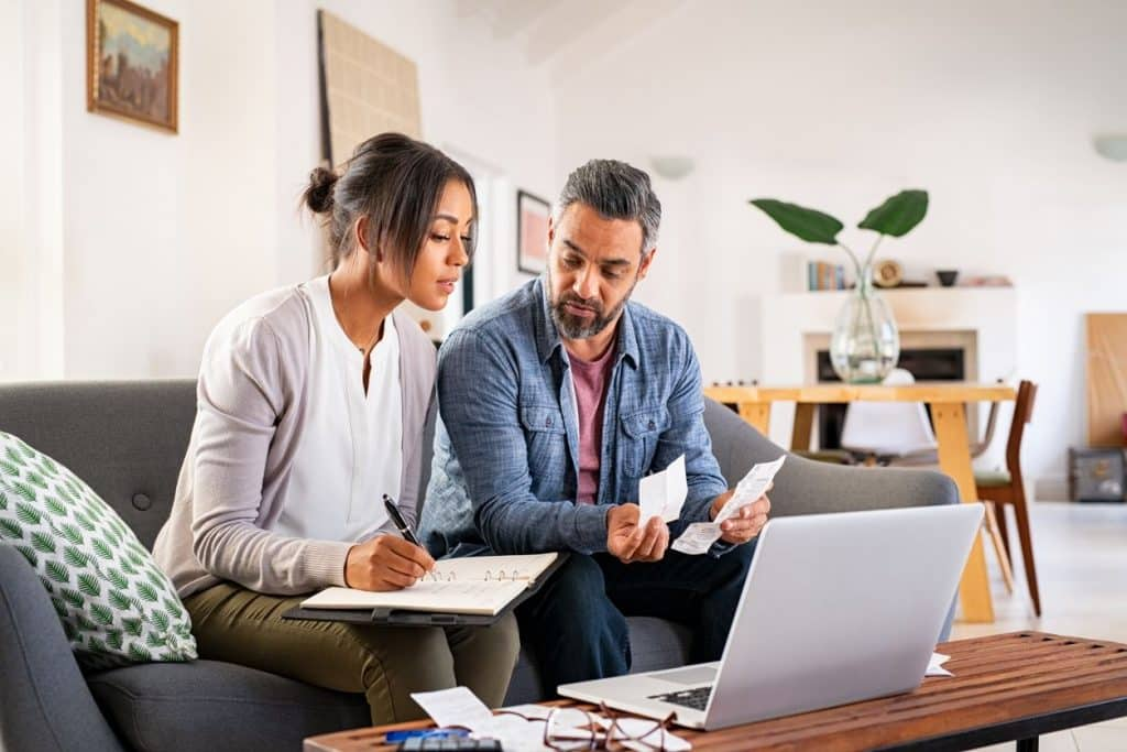 married couple at a computer staying on top of their finances