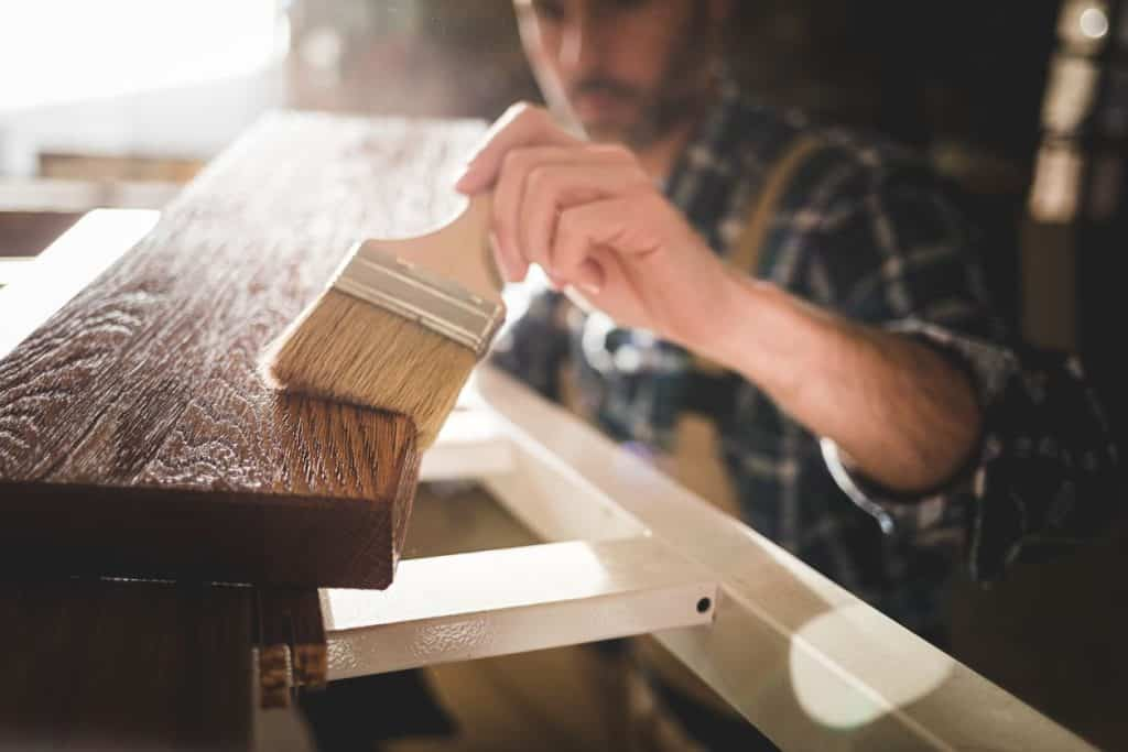 man putting finish on furniture that he's making and selling